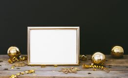 Mock up frame on wood rustic dark background with Christmas decorations glitter snowflakes, baubles, bell, serpentine and stars co Stock Image