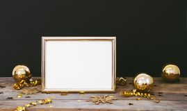 Mock up frame on wood rustic dark background with Christmas decorations glitter snowflakes, baubles, bell, serpentine and stars co Royalty Free Stock Image