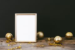 Mock up frame on wood rustic dark background with Christmas decorations glitter snowflakes, baubles, bell, serpentine and stars co Royalty Free Stock Photography