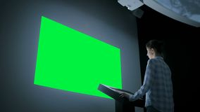 Green screen chroma key concept - woman looking at empty large wall display stock footage