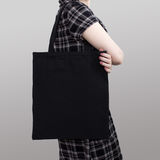 Mock-up. Girl in dress carries black cotton tote bag. Handmade eco shopping bag for girls stock images