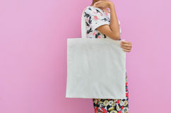 Mock-up Girl is holding blank cotton bag. Handmade eco shopping. Bag for girls and pink background stock images