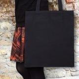 Mock-up. Girl in orange skirt holds black cotton tote bag. Handmade eco shopping bag for girls. Halloween mockups Stock Images
