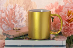 Mock-up of a golden mug. With some feminine stuff. For women`s gifts creators Royalty Free Stock Photography