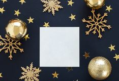Mock up greeteng card on black background with Christmas decorations ornaments glitter snowflakes, baubles and gold stars confetti Stock Image