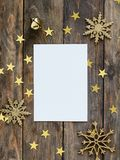 Mock up greeteng card on wood rustic background with Christmas decorations glitter snowflakes, bell and gold stars confetti. Invit Royalty Free Stock Photo