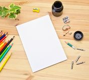 Mock up greeting card on the wooden background next to the pencils and pencil sharpeners, ink for drawing and calligraphy pens. Selective focus royalty free stock photography