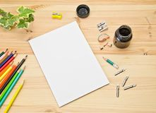 Mock up greeting card on the wooden background next to the pencils and pencil sharpeners, ink for drawing and calligraphy pens. Selective focus stock image