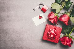 Mock up for greeting for Mothers day,birthday or Valentines Day.  Red gift box, ribbon, roses bunch , blank white paper. Love symb. Love symbols concept. Red Stock Photo