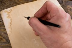 Mock up. Hand writing with old quill pen on the old paper. Empty place for a text. Copy space stock photography