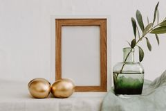 Mock Up Happy Easter. Gold eggs, frame and olive brunch. Over Linen Rustic Background Royalty Free Stock Images
