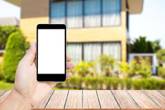 Mock up image of hand holding black mobile phone with blank white screen. Royalty Free Stock Photos