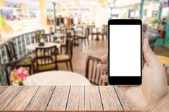 Mock up image of hand holding black mobile phone with blank white screen. Stock Photos