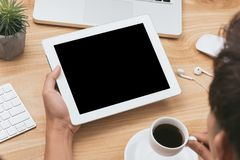 Mock up image of a hand holding black tablet pc with white blank screen and coffee cup on wooden table background royalty free stock image