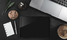 Mock-up image of laptop keyboard, tablet pc, a page on the note book and coffee cup on stone table Royalty Free Stock Photography