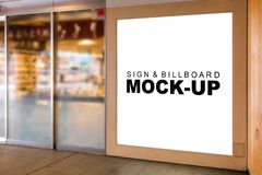 The mock up large wooden signboard at glass wall. The mock up large wooden signboard with modern design on glass wall with clipping path, blank white space for stock image