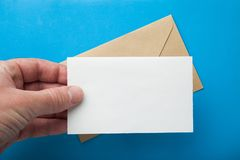 Mock-up of a letter in hand on the background of an envelope stock photography