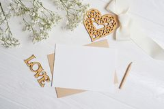 Mock up letter with a love box in the shape of a heart lies on a wooden white table with gypsophila flowers, a greeting stock photos