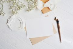 Mock up letter with a love box in the shape of a heart lies on a wooden white table with gypsophila flowers, a greeting card for V. Alentine`s Day with a place royalty free stock images