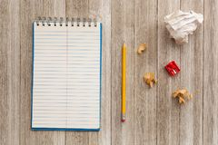Mock up with lined notepad, pencil, shavings and sharpener on wooden background stock photo