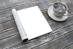 Mock-up magazine on the wooden table. A cup of hot coffee. Blank page or notepad for mockups or simulations royalty free stock photos