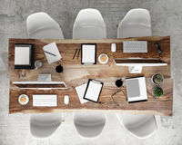 Mock up meeting conference table with office accessories and computers, hipster interior background,. 3D render Royalty Free Stock Photos