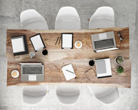 Mock up meeting conference table with office accessories and laptop computers, hipster interior background,. 3D render royalty free stock image