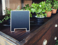 Mock up Menu Chalkboard stand with organic herb plants display on Wooden table Stock Photos