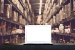 Mock up of modern computer or laptop with blank screen on table with Blurred boxes on rows of shelves in warehouse stock photo