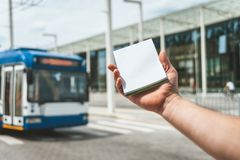 Mock Up notebook in a man`s hand, on the background of public transport and glass building. stock photos