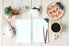 Mock up of open notebook, paper crafts, cube calendar, grilled carrots with scary face and coffee cup Stock Photos