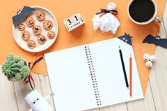 Mock up of open notebook, paper crafts, cube calendar, grilled carrots with scary face and coffee cup Stock Photography