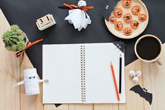 Mock up of open notebook, paper crafts, cube calendar, grilled carrots with scary face and coffee cup Stock Photo