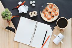Mock up of open notebook, paper crafts, cube calendar, grilled carrots with scary face and coffee cup Royalty Free Stock Image