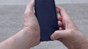 Man Using Mock Up Smartphone. Mock up phone being used by a man outside. Overhead stock video footage
