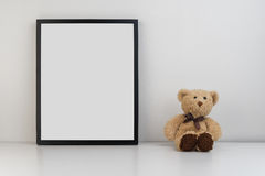 Mock up photo frame on table with a teddy bear as decoration Royalty Free Stock Images