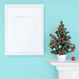 Mock up poster and christmas tree on a dresser with blue wall Stock Photo