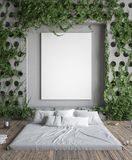 Mock up poster frame in hipster bedroom. Bed in floor and ivy on concrete walls. 3D render Royalty Free Stock Image