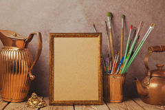 Mock up poster frame with vintage artistic objects on wooden table. Mock up poster frame with vintage artistic objects Royalty Free Stock Photos