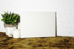 Mock up poster. Mock up poster on the table. White brick wall on background. Blank canvas for design stock images