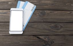 Mock up screen of the mobile phone stores air tickets. Modern technology, applications for smartphones,on a wooden background Royalty Free Stock Image