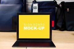 Mock up signboard with yellow screen in bag shop stock images