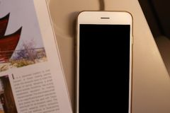 Mockup smartphone and book on plane passenger seat Royalty Free Stock Image