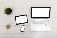 Mock up on a table with laptop, tablet, smartphone and a cup of stock photo