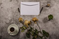 Mock up template with wilted flowers of white roses with a clean envelope, notepad and cup of coffee on a gray concrete background. View from above. Flat lay royalty free stock photography