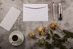 Mock up template with wilted flowers of white roses with a clean envelope, notepad and cup of coffee on a gray concrete background. View from above. Flat lay stock photos