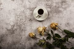 Mock up template with wilted flowers of white roses with a clean envelope, notepad and cup of coffee on a gray concrete background. View from above. Flat lay stock images