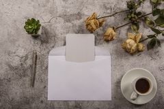 Mock up template with wilted flowers of white roses with a clean envelope, notepad and cup of coffee on a gray concrete background. View from above. Flat lay stock photography