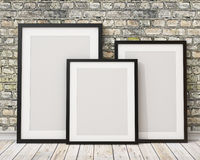 Mock up three blank black picture frames on the old brick wall and the wooden floor, background. 3d of three blank black picture frames on the old brick wall and Stock Photo