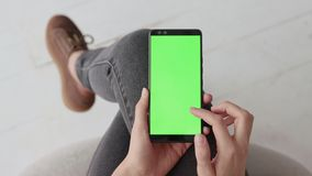Chroma key mockup with green screen on mobile phone of young woman at home